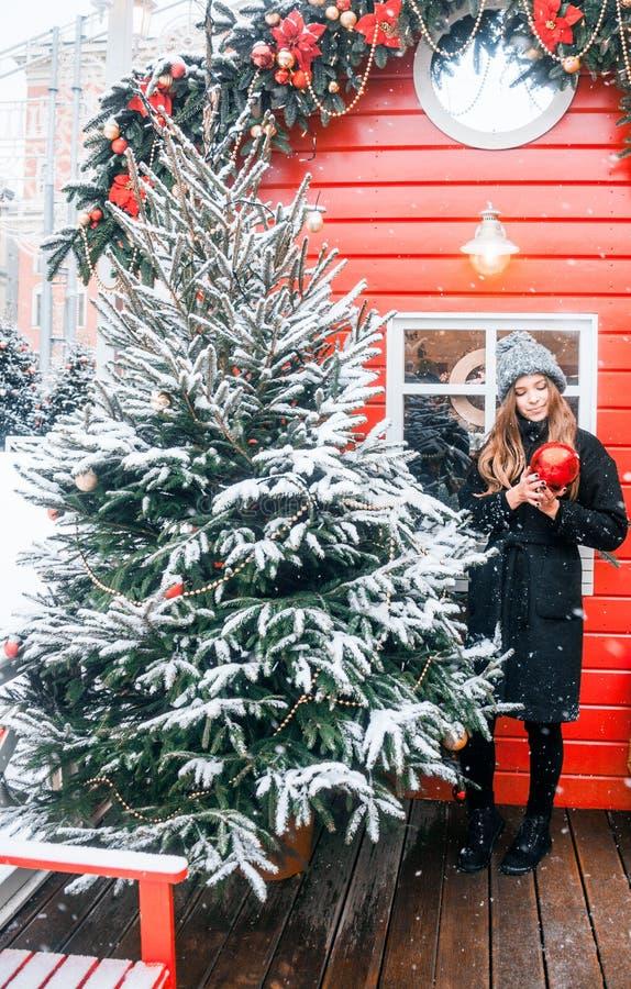 Bella ragazza russa in un giorno della nuvola in vestiti di inverno con la palla di natale in mani divertendosi nel quadrato di T immagini stock libere da diritti
