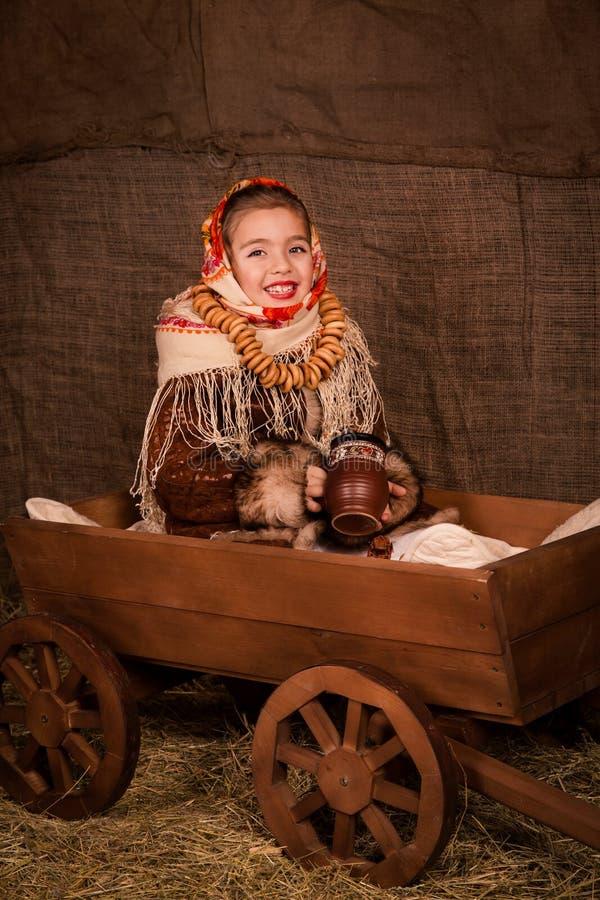 Bella ragazza russa in uno scialle che si siede in un carrello immagini stock libere da diritti