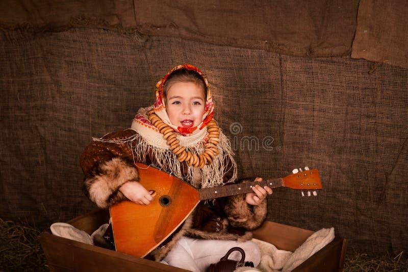 Bella ragazza russa in uno scialle che si siede in un carrello immagini stock