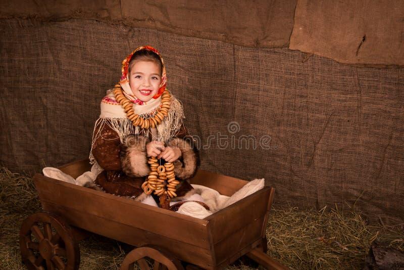 Bella ragazza russa in uno scialle che si siede in un carrello immagine stock libera da diritti