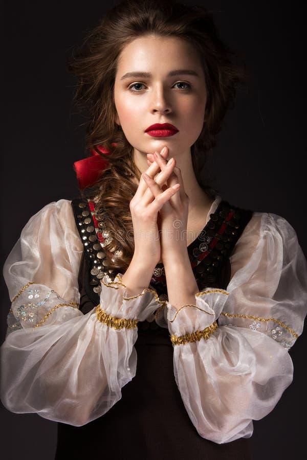Bella ragazza russa in vestito nazionale con un'acconciatura della treccia e le labbra di rosso Fronte di bellezza immagini stock