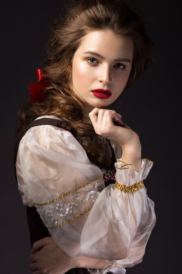 Bella ragazza russa in vestito nazionale con un'acconciatura della treccia e le labbra di rosso Fronte di bellezza fotografia stock libera da diritti