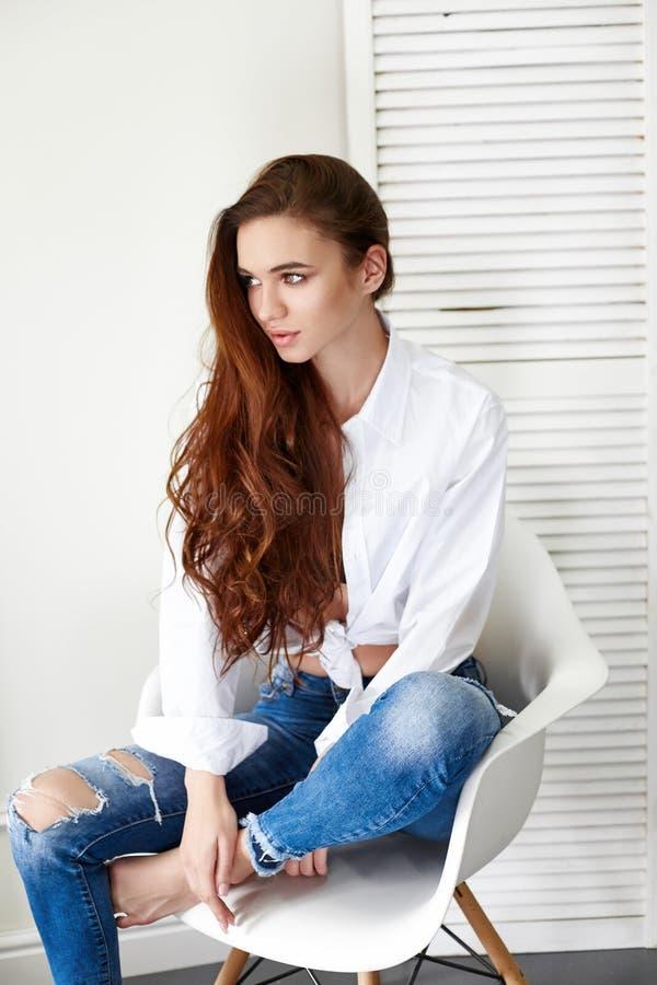 Bella ragazza sexy in camicia bianca dei jeans che si siede su una sedia Capelli lunghi splendidi e giovane donna incantante degl immagini stock