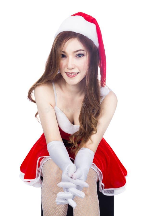 Bella ragazza sexy che indossa i vestiti del Babbo Natale e che si siede isolante fotografia stock