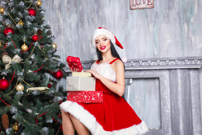 Bella ragazza sexy che porta i vestiti del Babbo Natale Donna sorridente con il grande e piccolo regalo Donne sul vestito e sul c fotografia stock libera da diritti