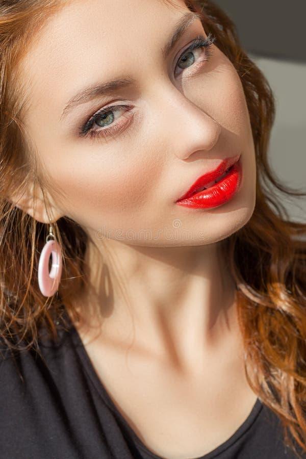 Bella ragazza sexy con capelli rossi con rossetto rosso e bello trucco in una maglietta nera un giorno di estate soleggiato lumin fotografia stock libera da diritti