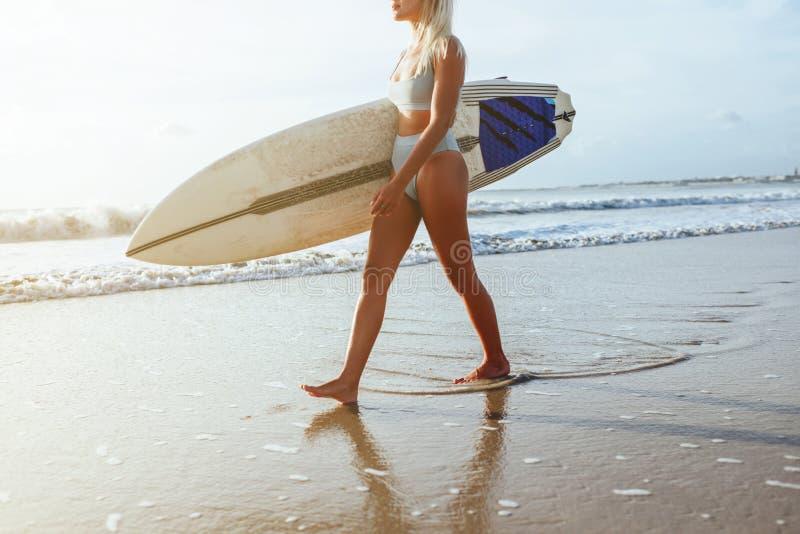 Bella ragazza sexy del surfista sulla spiaggia al tramonto immagine stock