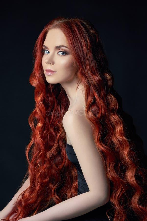 Bella ragazza sexy della testarossa con capelli lunghi Ritratto perfetto della donna su fondo nero Capelli splendidi e bellezza n fotografia stock