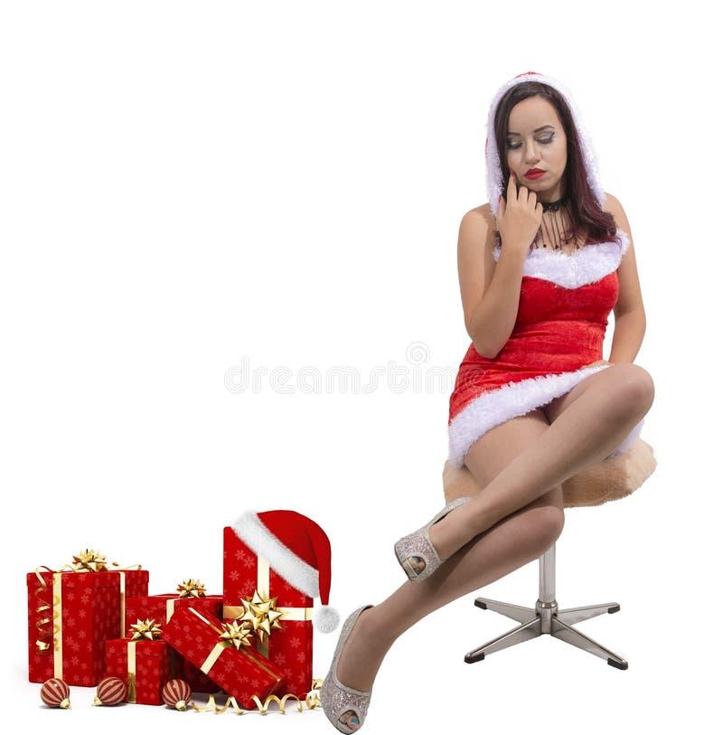 Bella ragazza sexy di Natale che indossa la regolazione del costume di Santa Claus sulla sedia accanto ai presente immagine stock libera da diritti