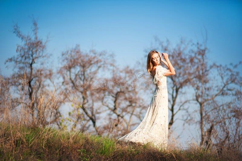 Bella ragazza snella con capelli marrone chiaro in un vestito leggero lungo su un fondo della natura, alberi asciutti, erba verde immagini stock libere da diritti