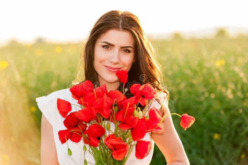 Bella ragazza sopra il cielo ed il tramonto nel campo che tiene un mazzo e sorridere dei papaveri fotografia stock libera da diritti