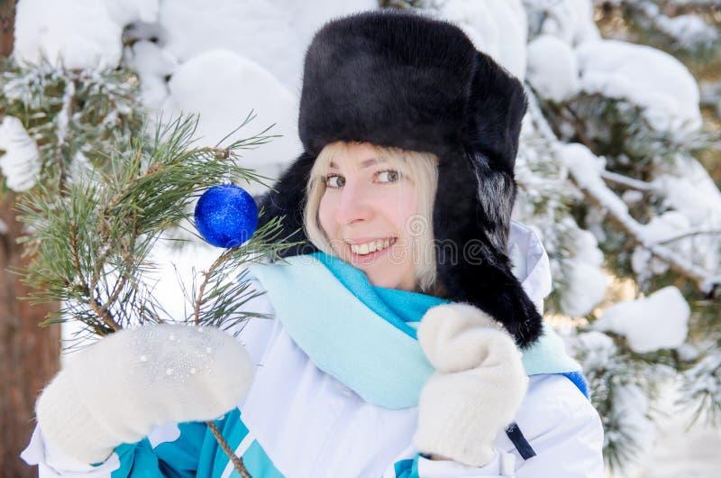 Bella ragazza sorridente bionda in un cappello di pelliccia caldo su fondo degli abeti nevosi nell'inverno fotografie stock