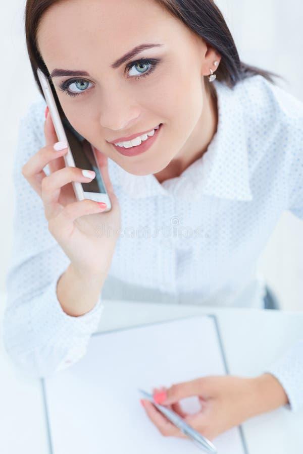 Bella ragazza sorridente che parla sul telefono cellulare nell'ufficio fotografia stock
