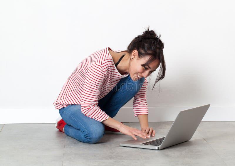 Bella ragazza sorridente che si siede sul pavimento, lavorante al computer fotografia stock
