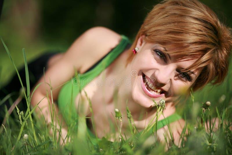 Bella ragazza sorridente che si trova sull'erba fotografia stock