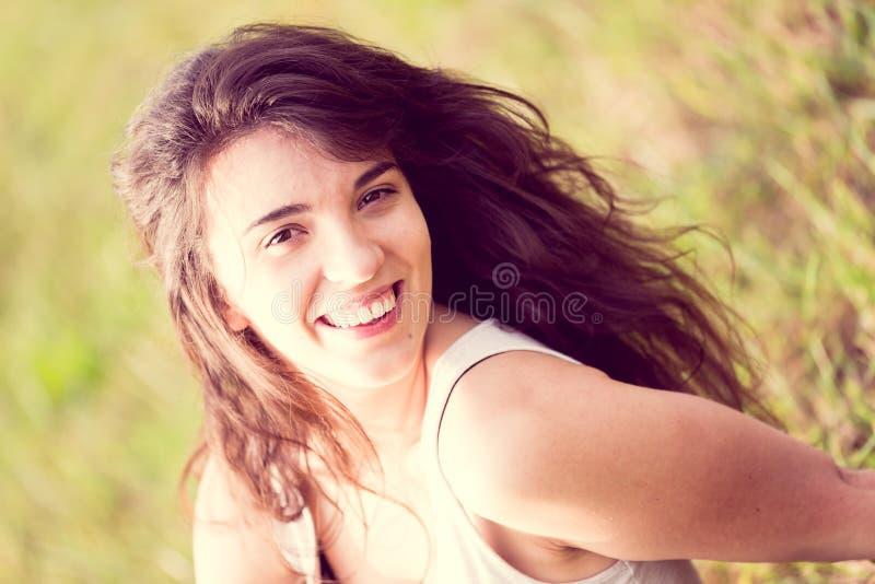 Bella ragazza sorridente con capelli neri lunghi nel giardino immagini stock libere da diritti