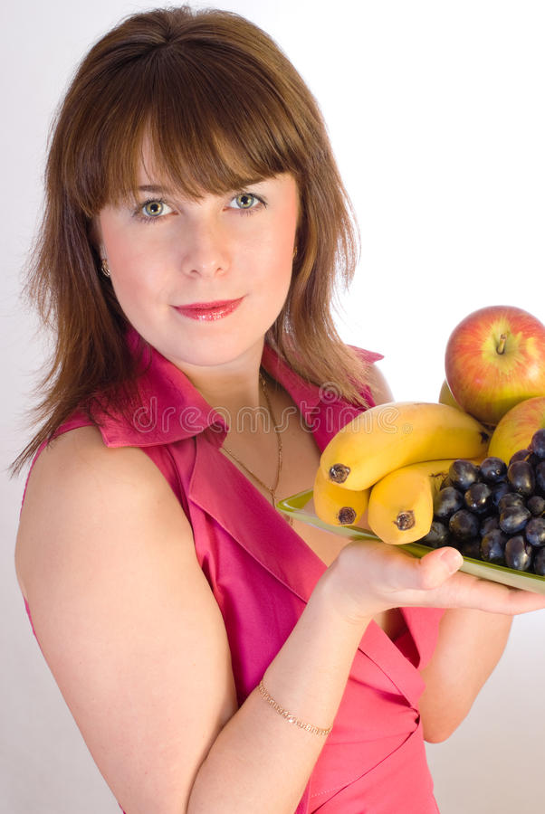 Bella ragazza sorridente con il piatto della frutta immagine stock libera da diritti
