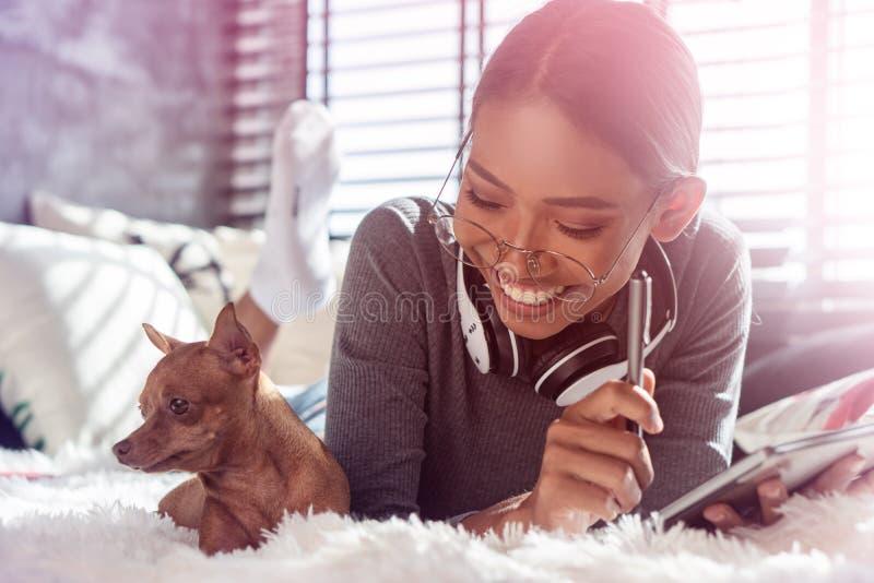 Bella ragazza sorridente con le cuffie e la compressa che si rilassano con il suo cane su un letto a casa immagine stock