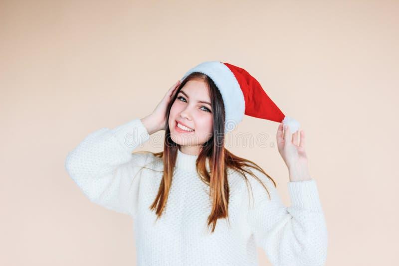 Bella ragazza sorridente con pelle pulita in cappello di Santa un maglione bianco accogliente su fondo beige fotografia stock libera da diritti