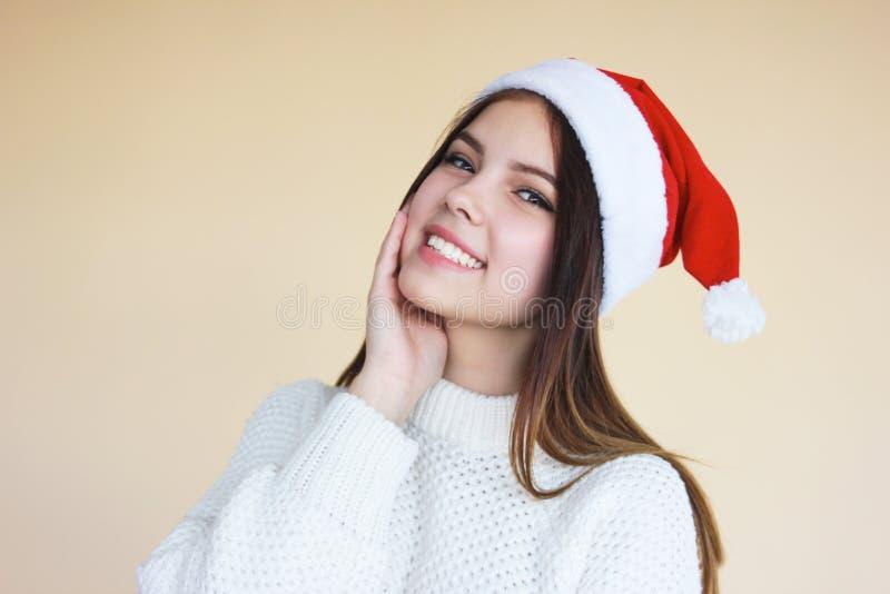 Bella ragazza sorridente con pelle pulita in cappello di Santa un maglione bianco accogliente su fondo beige immagine stock