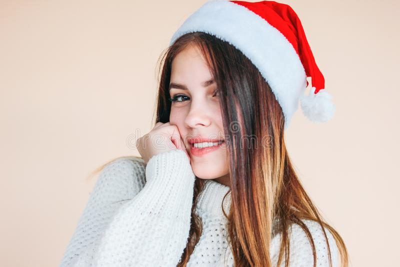Bella ragazza sorridente con pelle pulita in cappello di Santa un maglione bianco accogliente su fondo beige fotografie stock