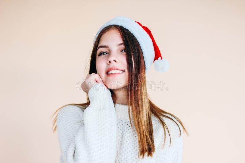 Bella ragazza sorridente con pelle pulita in cappello di Santa un maglione bianco accogliente su fondo beige fotografia stock