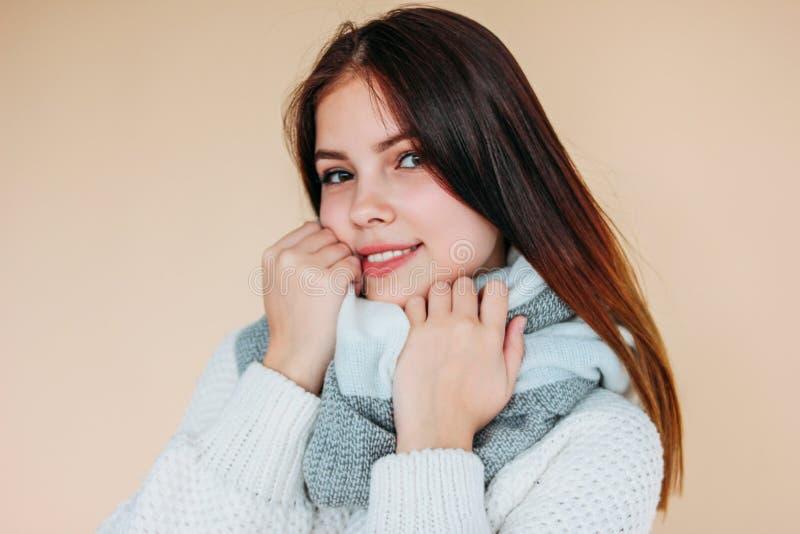 Bella ragazza sorridente con pelle pulita e capelli lunghi scuri in maglione bianco accogliente e sciarpa calda su fondo beige immagini stock