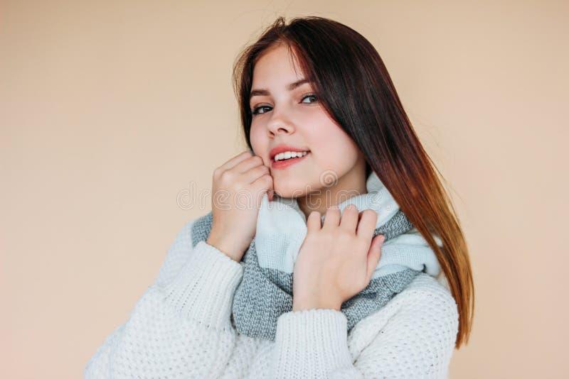 Bella ragazza sorridente con pelle pulita e capelli lunghi scuri in maglione bianco accogliente e sciarpa calda su fondo beige fotografie stock libere da diritti