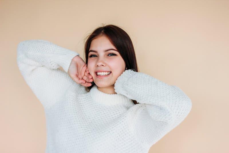 Bella ragazza sorridente con pelle pulita e capelli lunghi scuri in maglione bianco accogliente su fondo beige fotografia stock libera da diritti