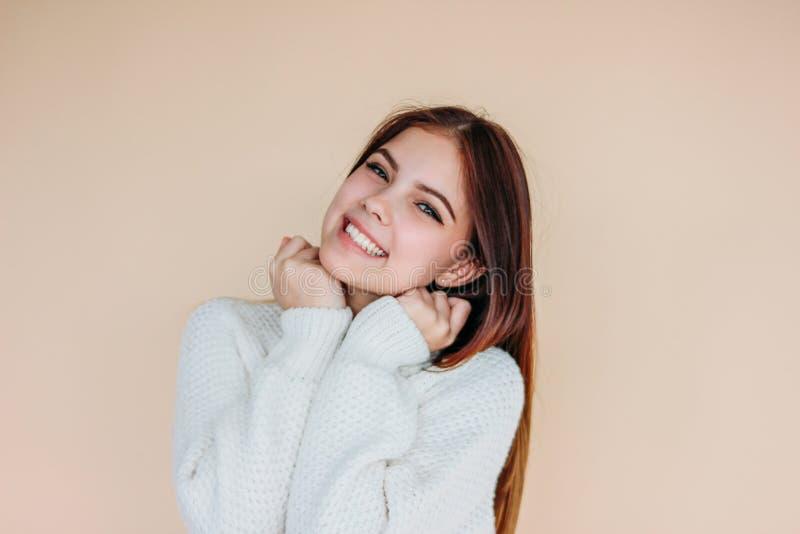 Bella ragazza sorridente con pelle pulita e capelli lunghi scuri in maglione bianco accogliente su fondo beige fotografia stock