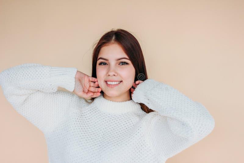 Bella ragazza sorridente con pelle pulita e capelli lunghi scuri in maglione bianco accogliente su fondo beige fotografie stock