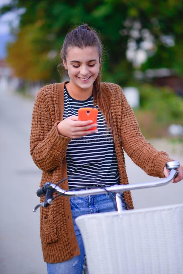 Bella ragazza sorridente con una bicicletta sulla strada immagini stock libere da diritti