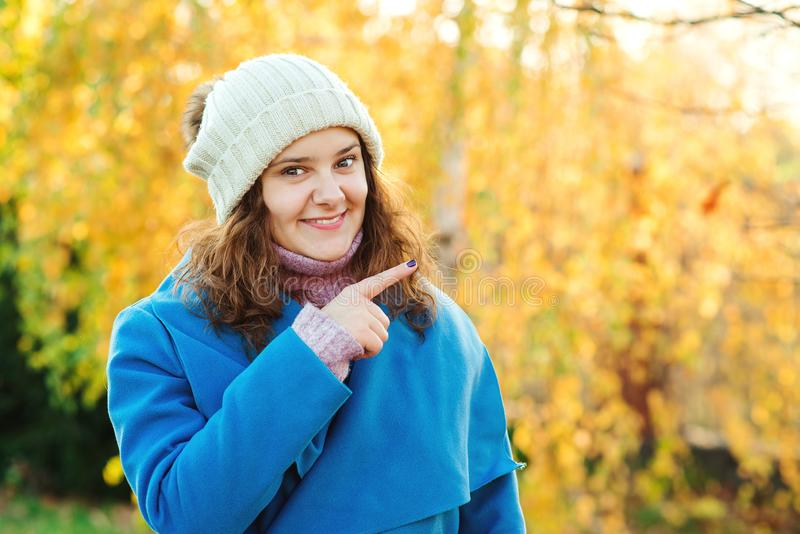 Bella ragazza sorridente sul fondo vago della natura di autunno Bella ragazza che indica il lato Copi lo spazio Emo facciale espr fotografia stock libera da diritti