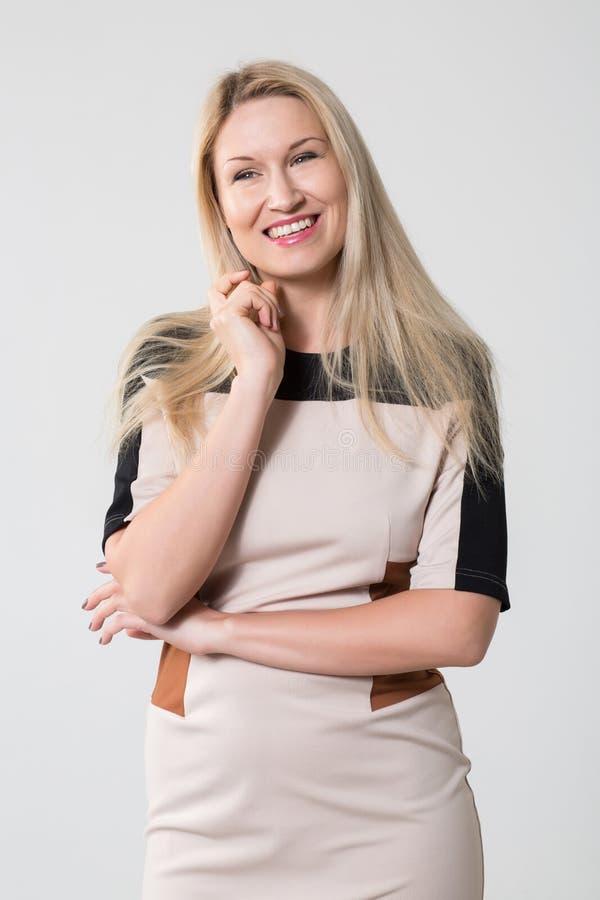 Bella ragazza sorridente in un vestito beige fotografia stock libera da diritti