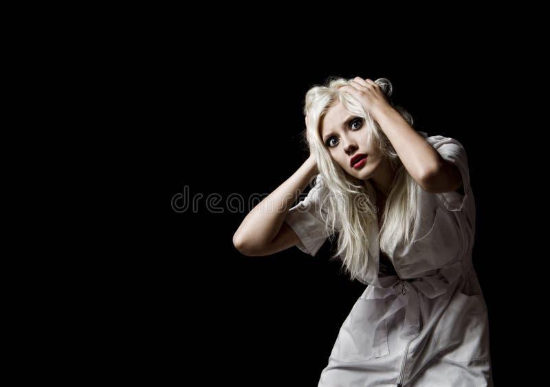 Bella ragazza spaventata nell'immagine dell'infermiere su fondo nero immagine stock libera da diritti