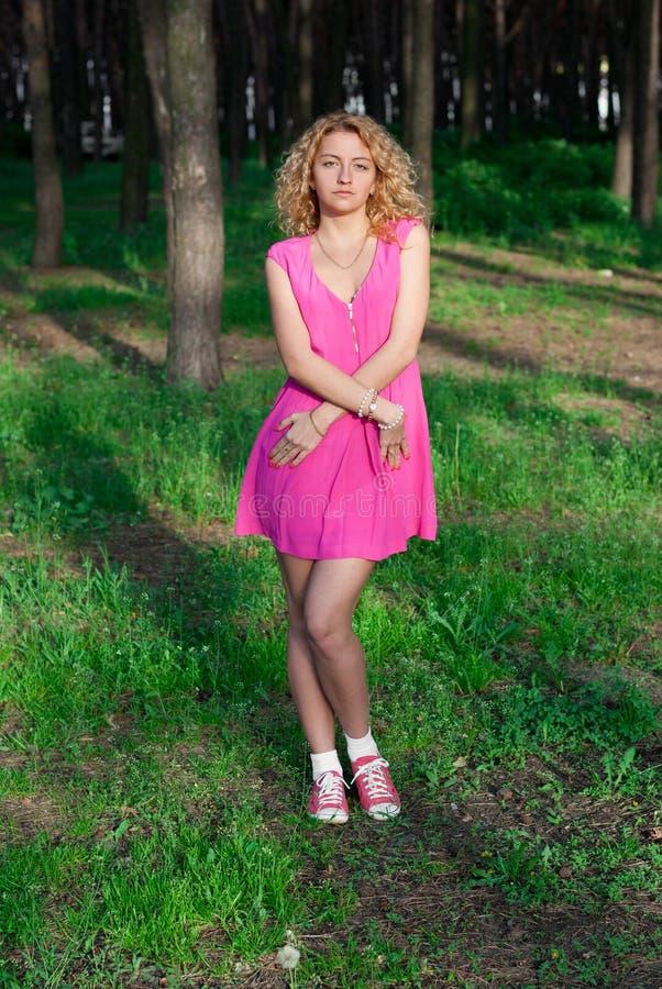 Bella ragazza su erba in foresta immagine stock