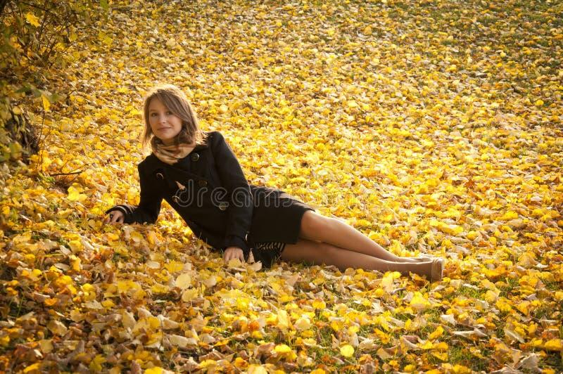 Bella ragazza sui fogli gialli caduti fotografia stock libera da diritti