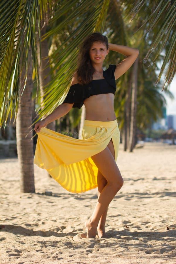 Bella ragazza sui supporti della spiaggia vicino alla palma fotografie stock