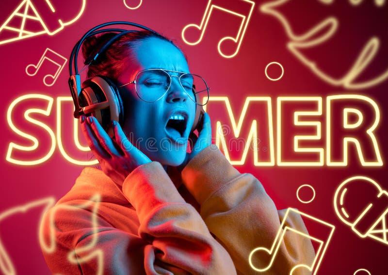 Bella ragazza sul fondo dello studio alla luce al neon fotografia stock libera da diritti
