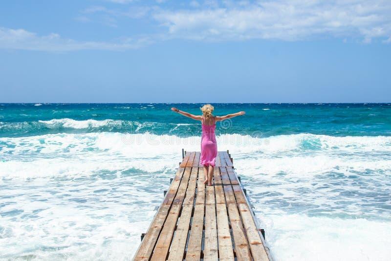 Bella ragazza sul pilastro della riva di mare fotografia stock