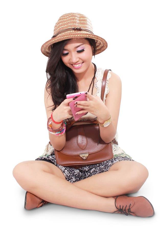 Bella ragazza sulla vacanza e sul telefono cellulare di gioco fotografia stock libera da diritti
