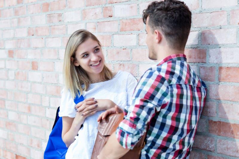Bella ragazza tedesca tedesca bionda che parla con lo studente maschio immagine stock libera da diritti