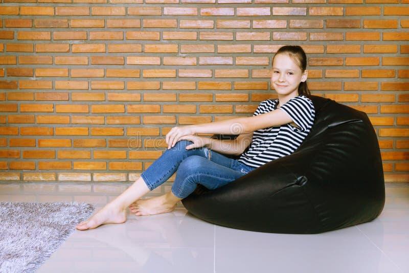 Bella ragazza teenager caucasica che si siede nella sedia della borsa di fagiolo nero contro il muro di mattoni Attrezzatura casu immagini stock