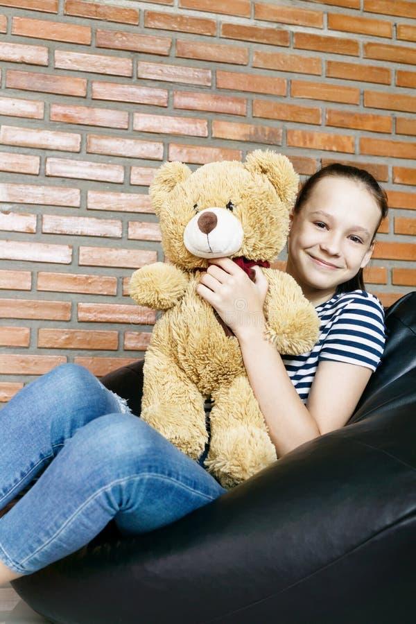 Bella ragazza teenager caucasica che si siede nella sedia della borsa di fagiolo nero che tiene il grande giocattolo marrone dell immagine stock libera da diritti