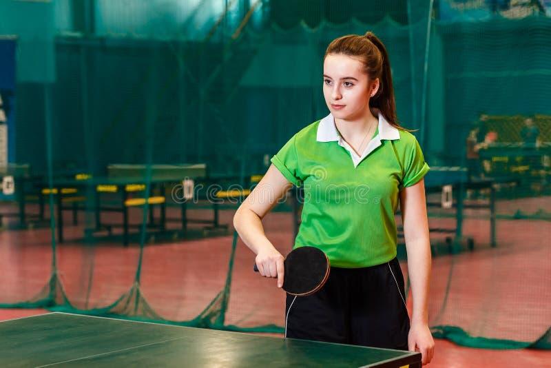 Bella ragazza teenager caucasica di quindici anni in maglietta verde di sport che impara giocare ping-pong fotografie stock