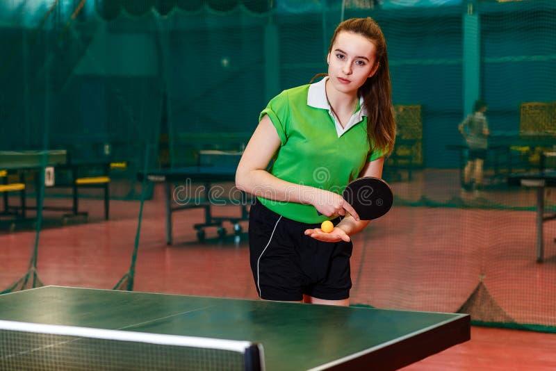 Bella ragazza teenager caucasica di quindici anni in una maglietta verde di sport che tiene una racchetta di tennis e una palla e fotografia stock
