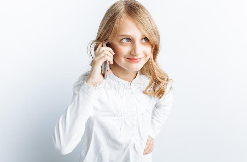 Bella ragazza teenager che parla sul telefono cellulare, studio della foto, isolato immagine stock libera da diritti