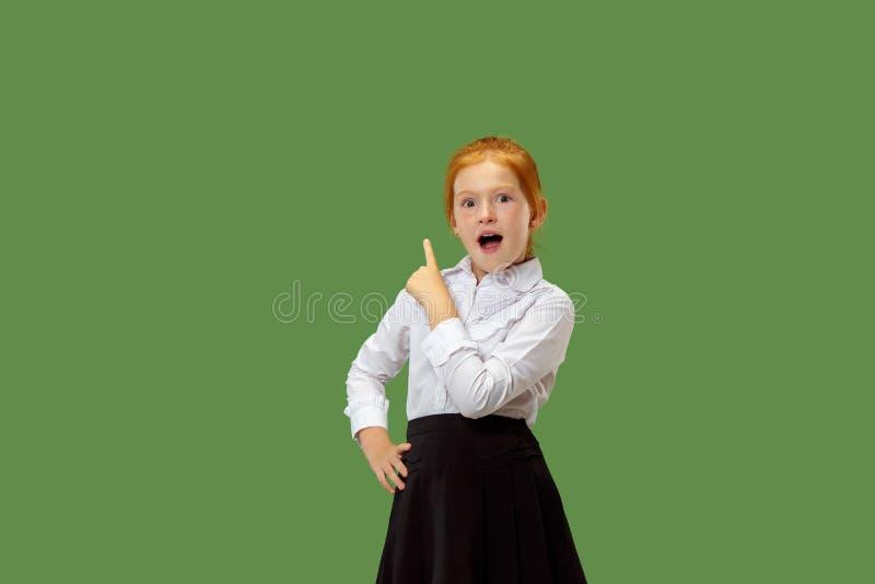 Bella ragazza teenager che sembra sorpresa isolato su verde immagini stock libere da diritti