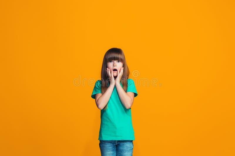Bella ragazza teenager che sembra sorpresa isolato sull'arancia immagini stock