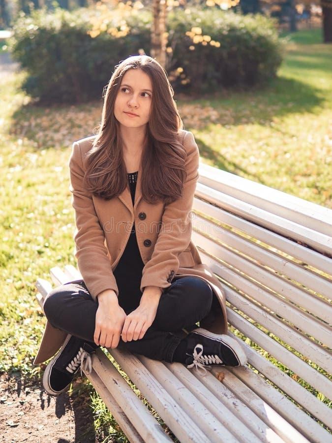 Bella ragazza teenager che si siede nel parco su un banco, sognante, Th immagini stock libere da diritti